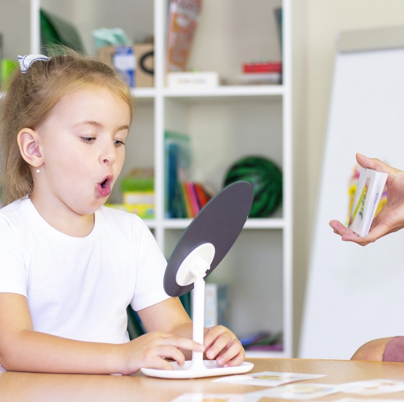 developmental and speech therapy classes with a child-girl. Speech therapy exercises and games with a mirror and cards